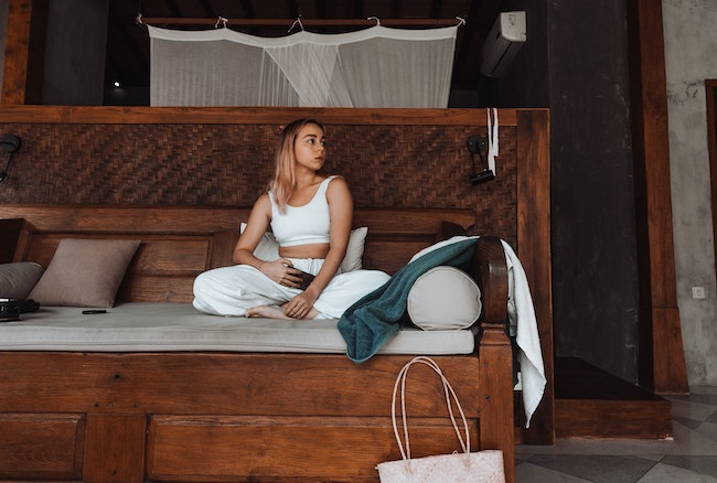 Woman in a master bedroom sitting on the Best Mattress Topper, Australia (2020)