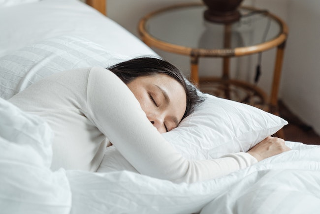 Woman in white sleeping on the Best Mattress for Side Sleepers, Australia